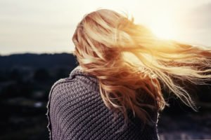 woman facing the sun with her hair blowing