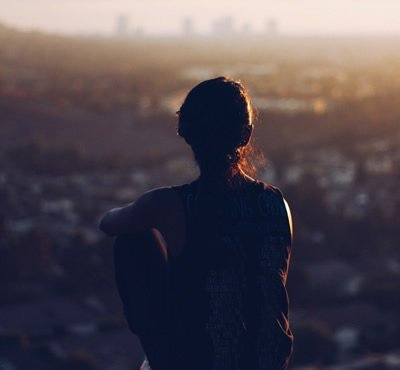woman sitting at peace overlooking the city